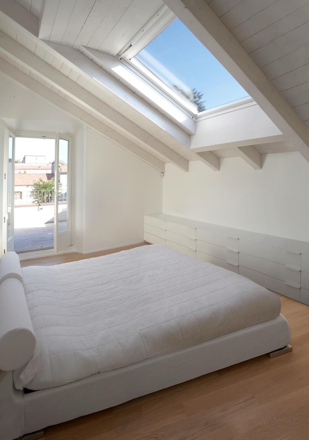 La camera da letto illuminata da finestre per tetti