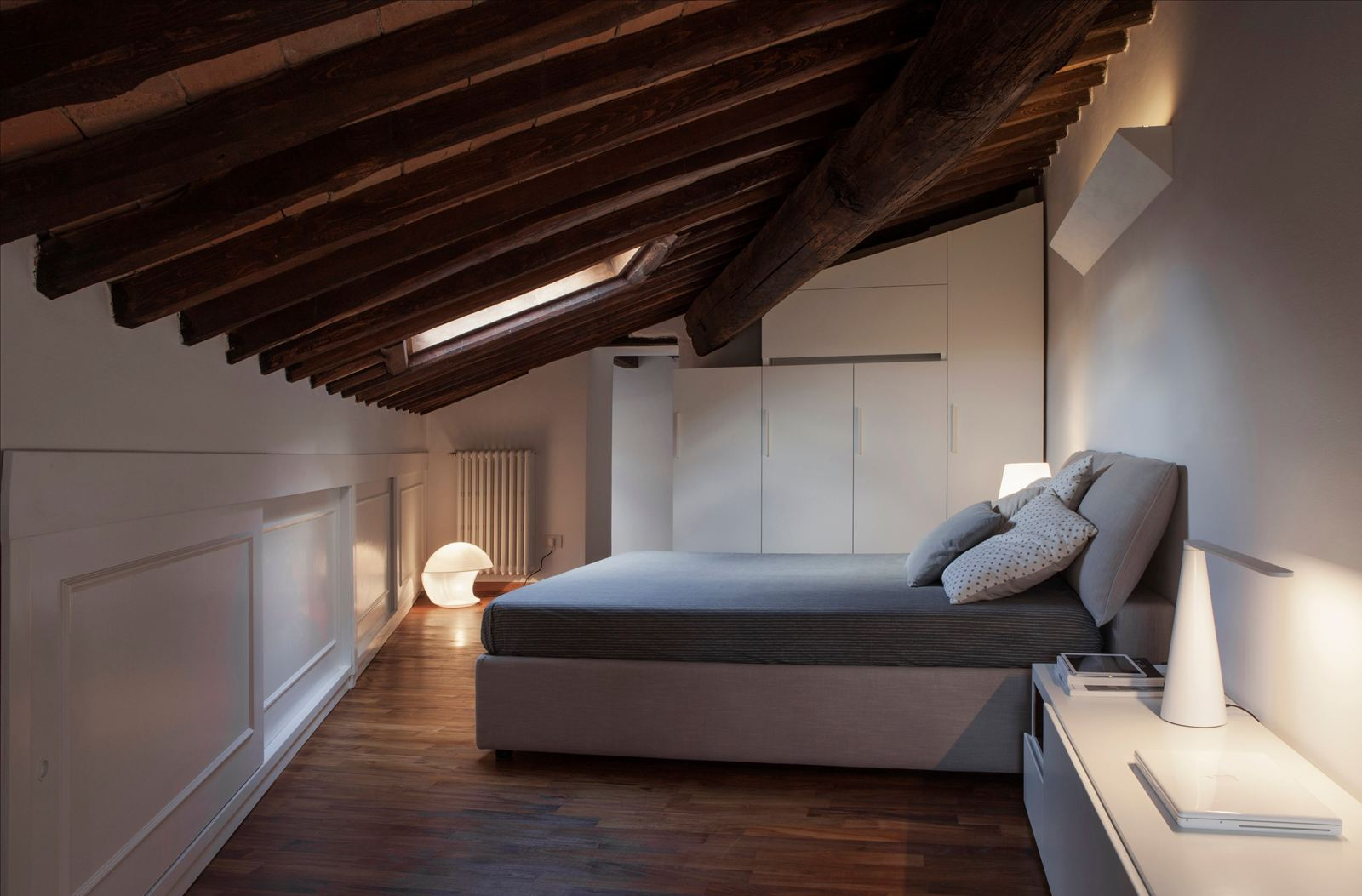 Binomio legno bianco per una mansarda a lucca for Faretti camera da letto