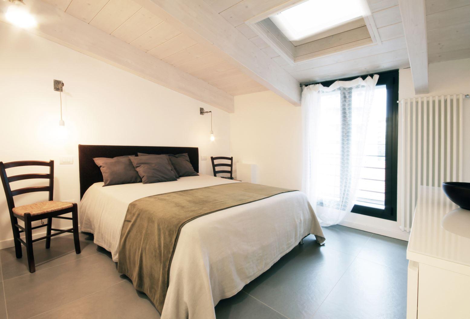 Una mansarda con il tetto in legno a milano - Camera da letto sottotetto ...