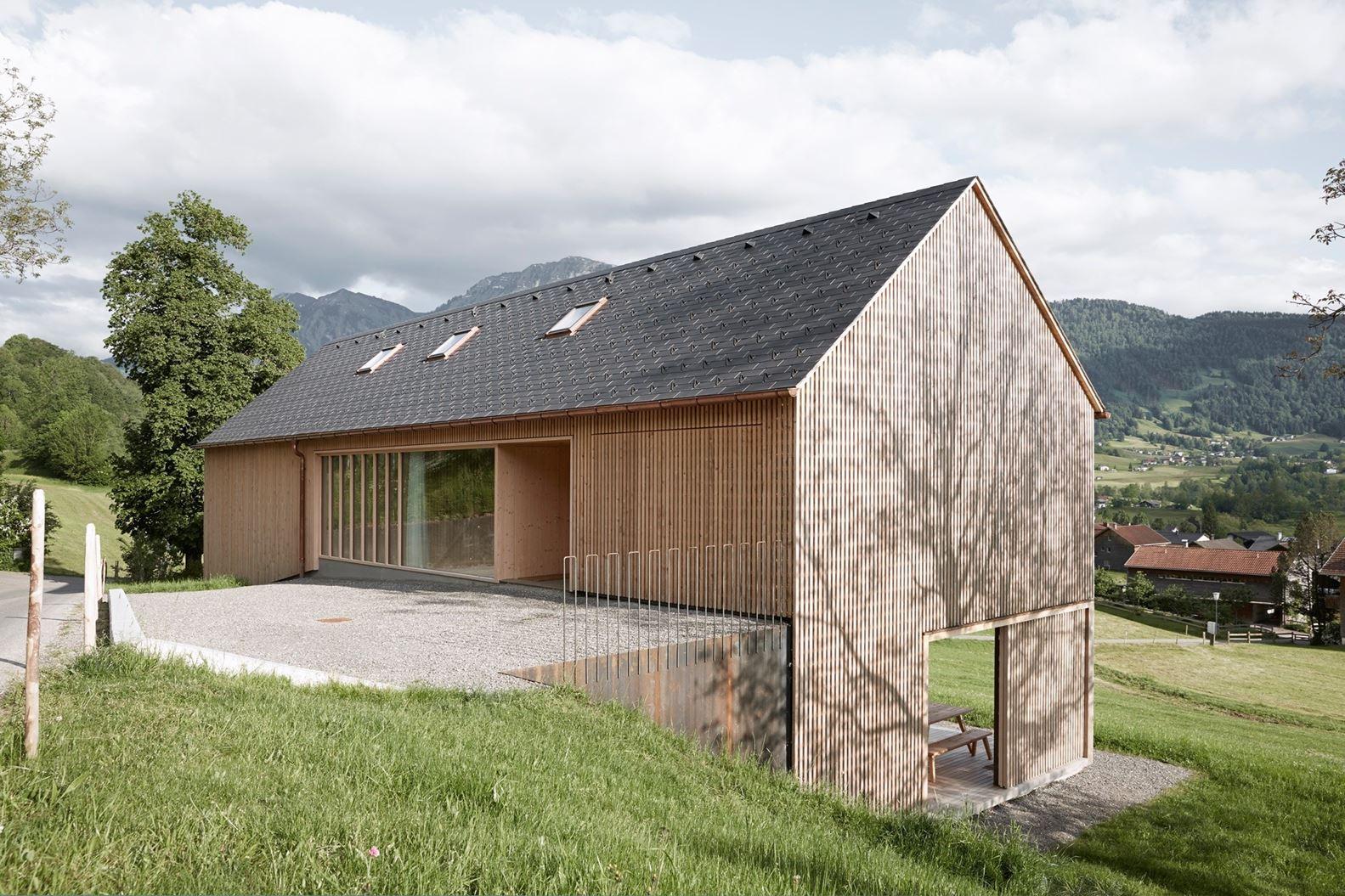 Una casa in legno con ampie vetrate for Piani di casa in collina con garage sottostante