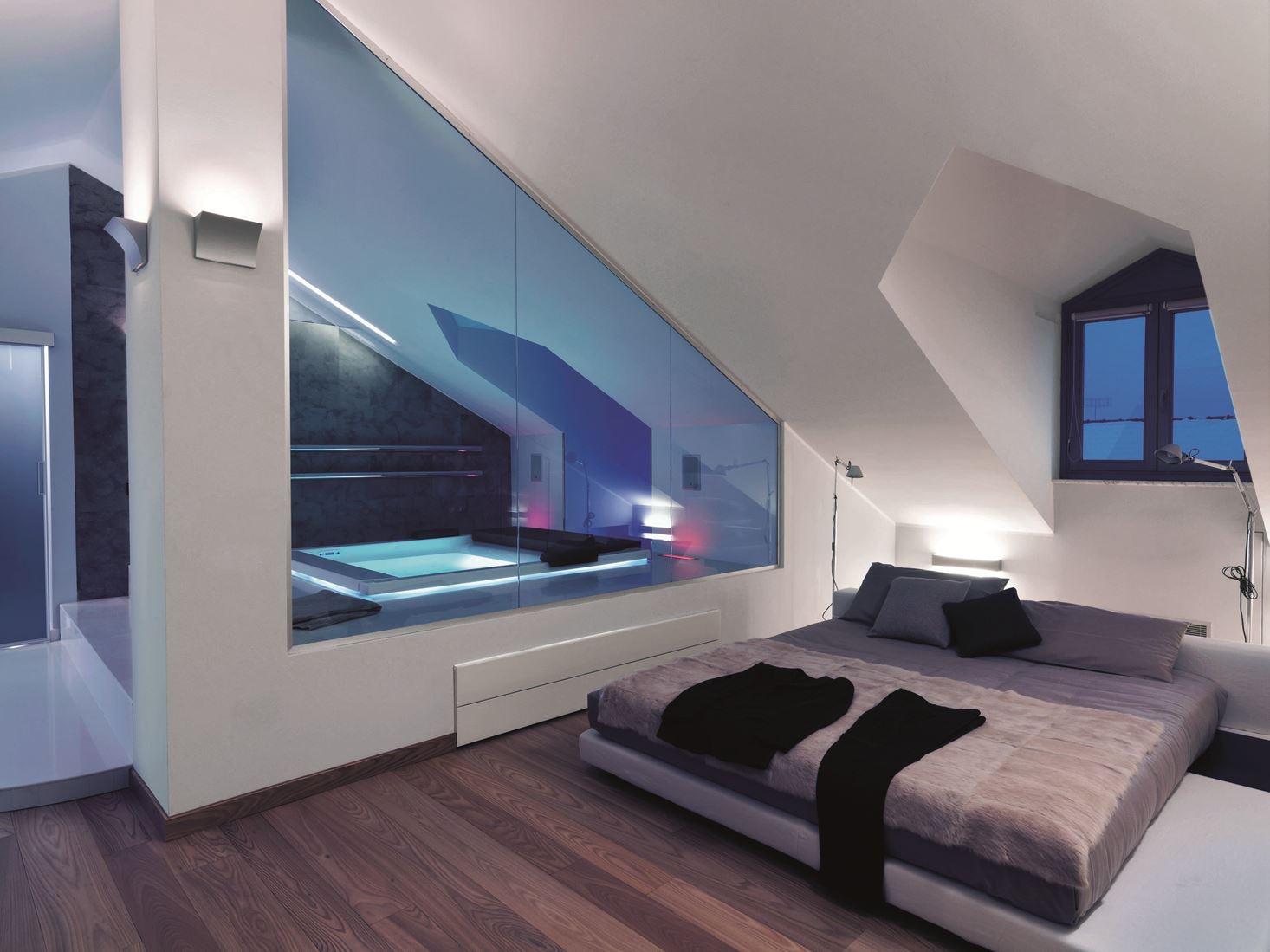 small attic renovation pictures - Un attico con finestre per tetti e ampie vetrate Mansarda