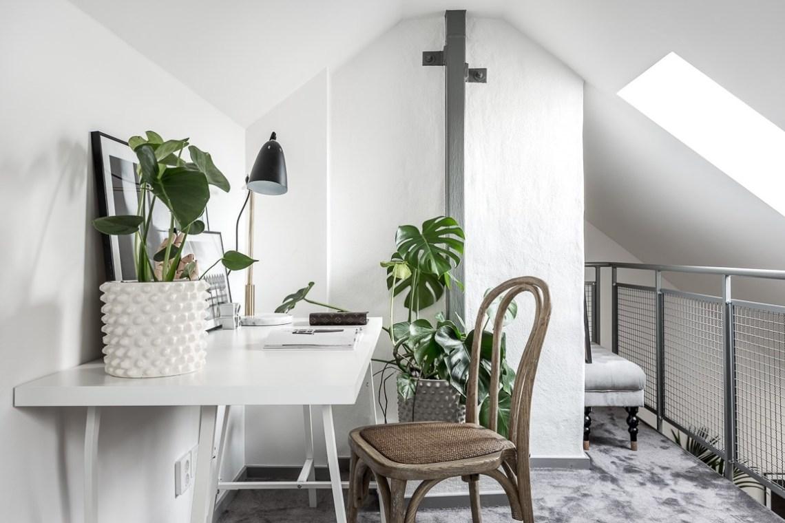 Una scrivania, una sedia e molte piante per questo studio in mansarda