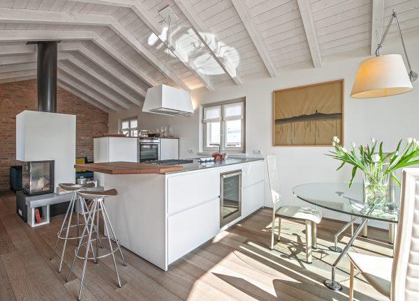 Una cucina open space con elementi a vista
