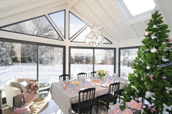 La veranda con il tavolo imbandito per le feste, illuminato dalla luce naturale.