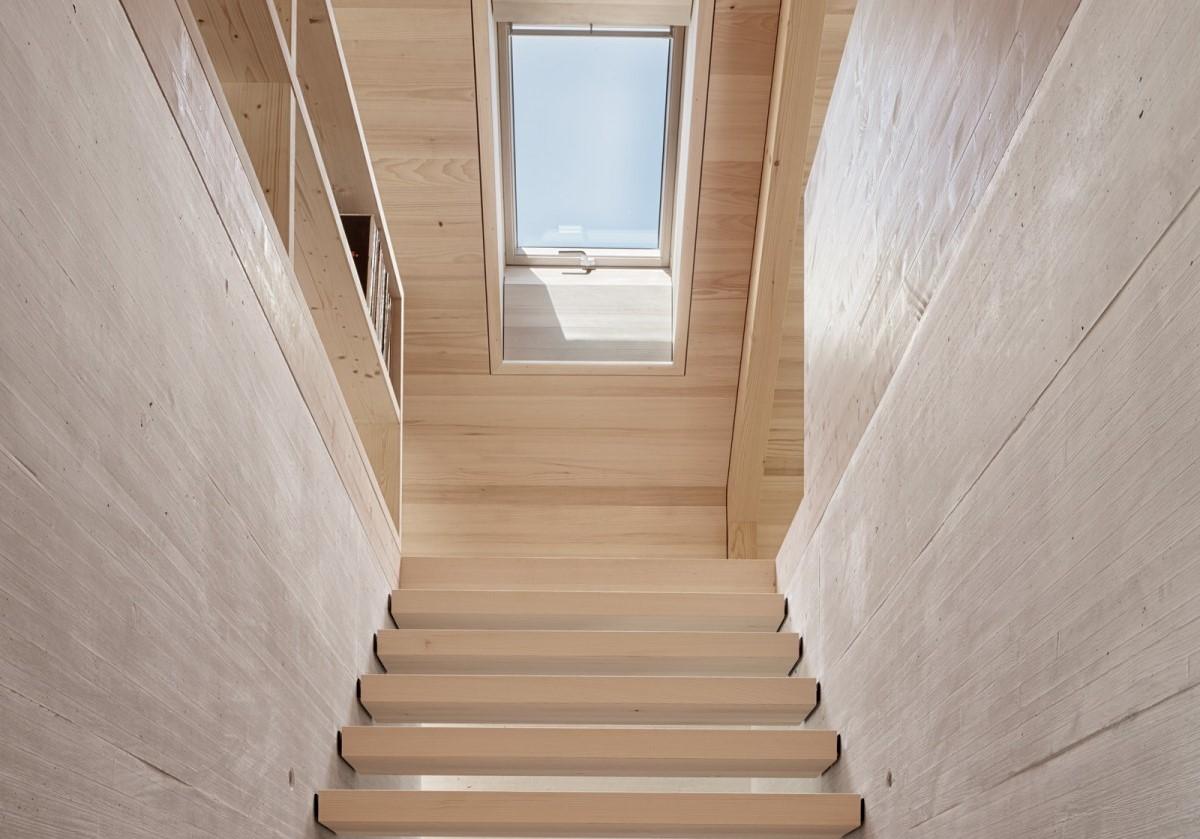 Scala moderna in legno illuminata da una finestra per tetti